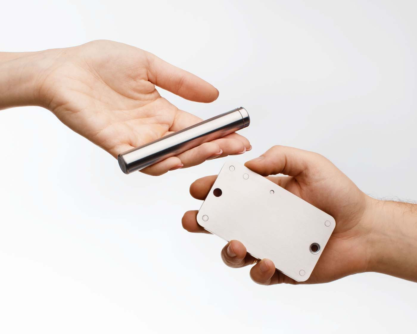 Two hands holding a Cryptosteel Capsule and a Cryptosteel Cassette